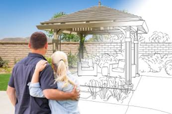 a couple looking at a blueprint project of Toowoomba Carports being built